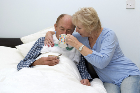 Elderly bedridden man being given a drink by his carer and wife