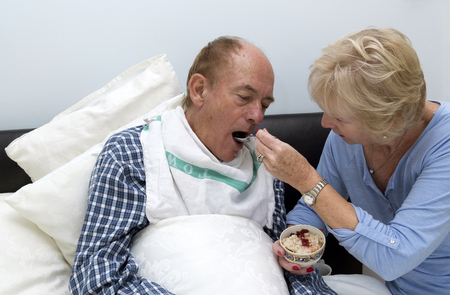 An elderly sick bedridden man being fed breakfast by his wife and carer