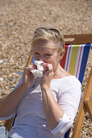 Woman sitting in a deckchair at the seaside suffering from a runny nose. Blowing her nose