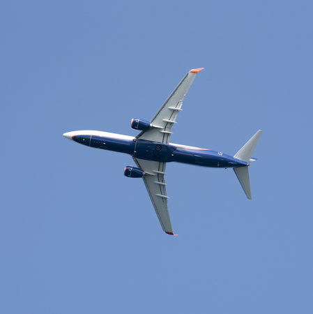 Underside of a Russian twinjet taking off against a blue sky