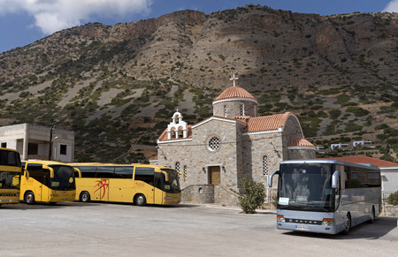 Tour buses parked outside a modern Greek church in the small coastal town of Plaka, Lasithi region of Crete, Greece, October 2017.
