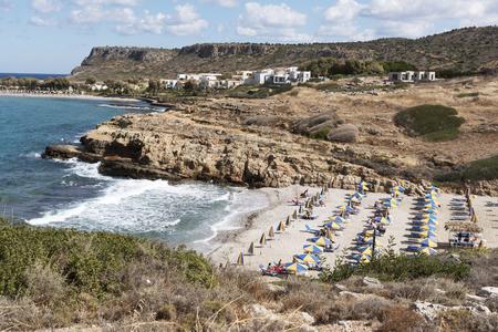 Beach and sunshades on the Cretan seaside resort of Sisi close to Malia, Crete, Greece. October 2017