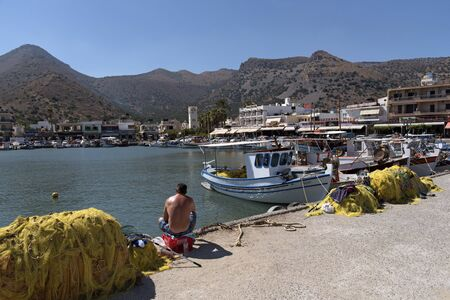 A man fishing at the fishing boat harbour at Elounda a seaside resort in northern Crete, Greece. October 2017 Editorial