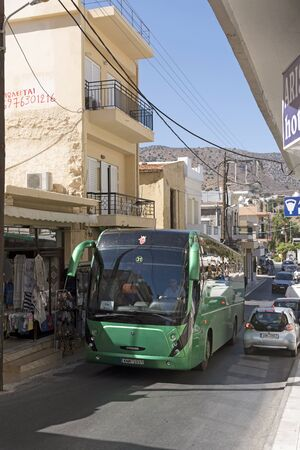 Narrow main street in Elounda, Lasithi region in Crete, Greece. October 2017.  A tour bus passing a line of traffic