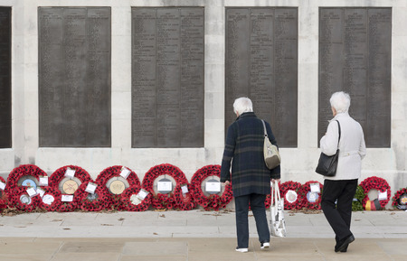 Naval War memorial, Plymouth Hoe, Plymouth, Devon, England UK. November 2017. Visitors looking at the poppy wreaths standing in line