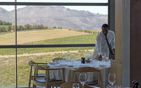 West-Kaap regio Zuid-Afrika. Circa 2017. Ober tot een restaurant tafel die een schilderachtig uitzicht op wijnstokken en bergen heeft