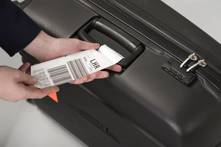 Airline luggage security tag being attached to a travellers black suitcase