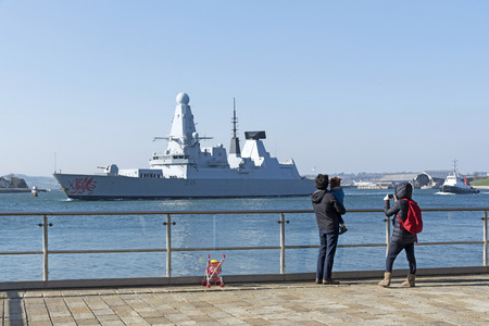 Plymouth, Devon, England, UK. HMS Dragon a type 45 Daring Class air defence destroyer departing Devonport. Watched by a young familey. February 2018 Editorial