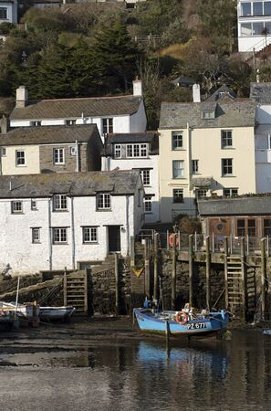 Polperro harbour, Cornwall, England, UK. February 2018. A small blue painted fishing boat at low tide in this famous little harbour