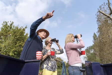 Group of people on a boating holiday using binoculars to spot wildlife along the Wilts & Berks Canal at Swindon UK