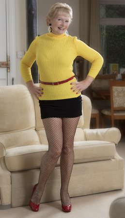 Attractive woman in her sixties wearing a mini skirt and yellow jumper Stockfoto