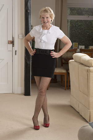 Attractive woman in her sixties wearing a mini skirt and white shirt Standard-Bild