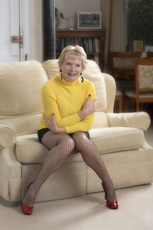 Attractive woman in her sixties wearing a mini skirt and yellow jumper sitting on a sofa 写真素材 - 98221000