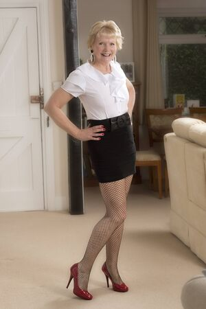 Attractive woman in her sixties wearing a mini skirt and white shirt Stock Photo