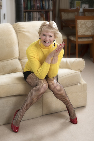 Attractive woman in her sixties wearing a mini skirt and yellow jumper sitting on a sofa