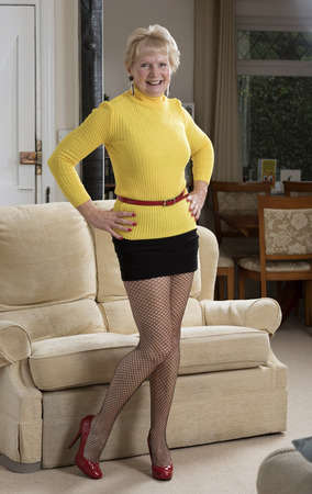 Attractive woman in her sixties wearing a mini skirt and yellow jumper Foto de archivo