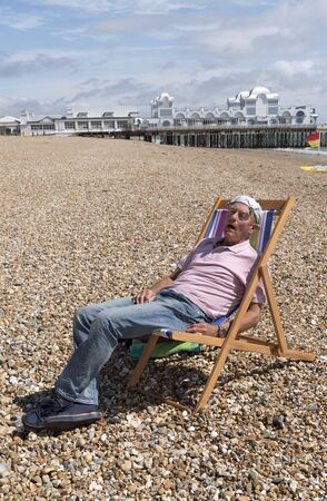 Elderly man wearing a knotted hankerchief on his head relaxing on the beach. Southsea, England UK Stock Photo