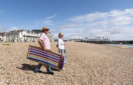 Elderly couple walking with a deckchair on a shingle beach. Southsea, England UK