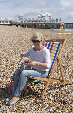 Woman sitting in a deckchair on the beach on a windy day. Southsea, England UK Stock Photo