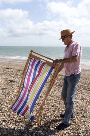 Elderly man in a straw hat erecting a deckchair on a pebble beach in southern England UK