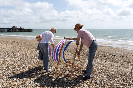 Elderly couple on holiday erect a deckchair on a windy day. Southsea southern England UK