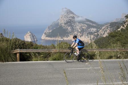 Mirador de la Creueta, Formentor, Majorca, Balearic Islands, Spain, 2018, Road cyclist  at a lookout point El Colomer along the PM 221 road.