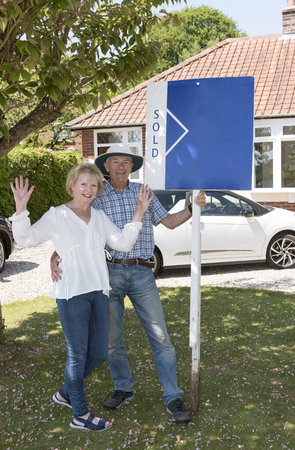 Couple standing with a sold sign outside their home Banco de Imagens