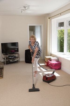 Moving home, Woman using a vacum cleaner to hoover the carpet and doing leg stretch exercises