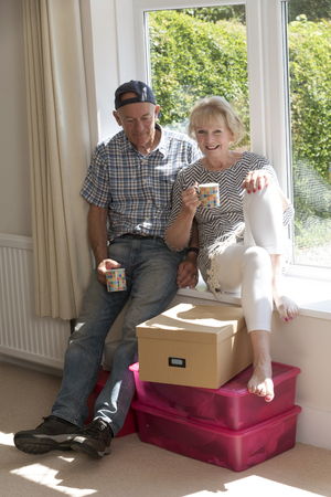 Elderly couple sitting on a window seat in their home relaxed and drinking mugs of coffee