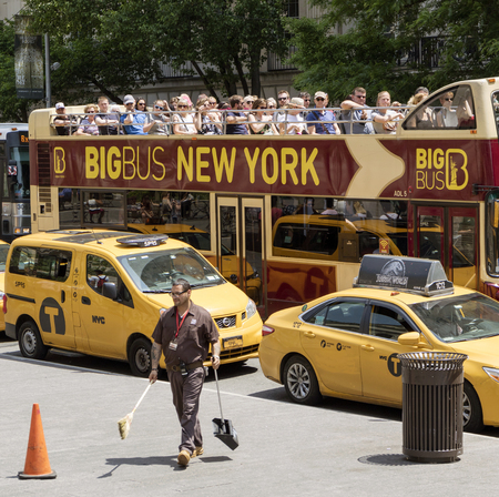 New york USA. Uniformed man from The MET with dustpan and brush sidewalk cleaning outside this famous museum watched bus load of tourists. Redactioneel