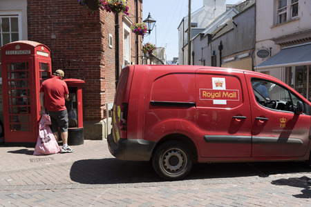 Postal worker emptying a red letterbox in Sidmouth town centre, Devon, UK
