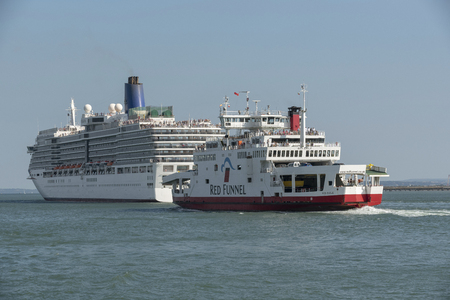 An Isle of Wight roro ferry passing close to the Arcadia cruise ship on Southampton Water, England, UK