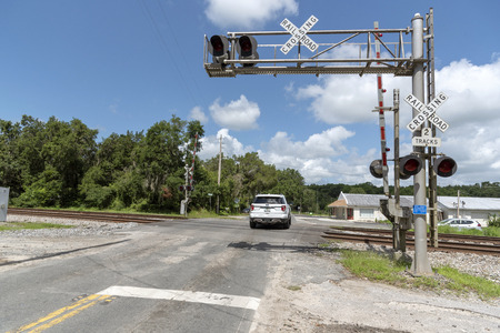 Summerfield, Florida, USA, 2018. Railroad signals and track passing through North Florida countryside. Car crossing the junction. Foto de archivo - 109865207