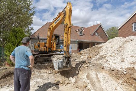 Una excavadora sobre orugas cavando una zanja para un tanque subterráneo en una urbanización en Hampshire, Inglaterra, Reino Unido.