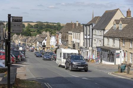 Burford Oxfordshire, England, UK. Car towing a caravan on the main street