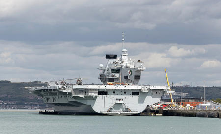 Portsmouth UK. Saturday 18 August 2018. HMS Queen Elisabeth seen yesterday afternoon preparing to depart Portsmouth Dockyard southern England UK on deployment to the USA for further sea trials. She will depart this evening. Picture: Peter Titmuss/ Alamy