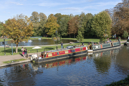 Narrowboats and autumn colours along the banks of the Kennet and Avon Canal at Newbury, Berkshire, England UK.