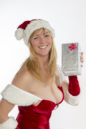 Blond woman in a revealing red costume with a present at christams time