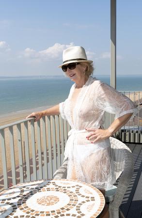 Donna anziana in piedi su un balcone in riva al mare. Inghilterra meridionale del Regno Unito