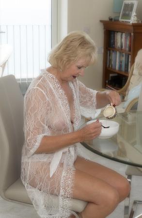 Donna anziana attraente che mangia prima colazione. Archivio Fotografico