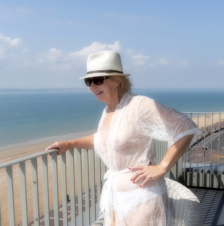 Elderly woman standing on a balcony at the seaside. Southern England UK