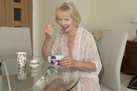 Elderly woman in see through dressing gown eating breakfast Stok Fotoğraf