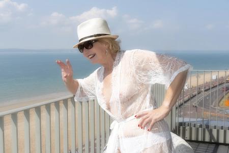 海辺のバルコニーに立つ高齢の女性。南イングランド英国