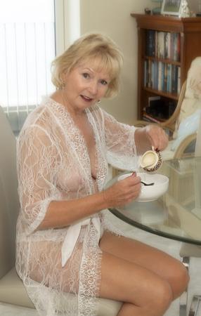 Donna anziana attraente che mangia prima colazione.