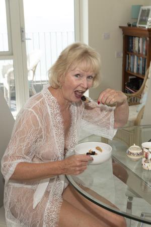 Attractive elderly woman eating breakfast.