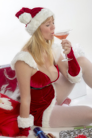 Blond woman wearing a santa fancy dress costume and holding a drink