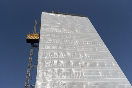 Highrise block of flats and apartments covered in plastic sheeting for weather protection whilst work is carried out on the building, Gosport, Hampshire, UK
