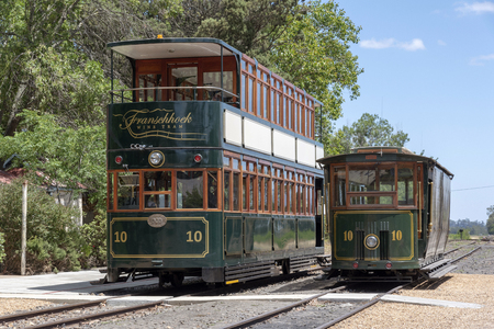 A single and double deck wine tram at the Groot Drakenstein depot near Franschhoek in the Western Cape, South Africa. Trams take tourists on vineyard tours.