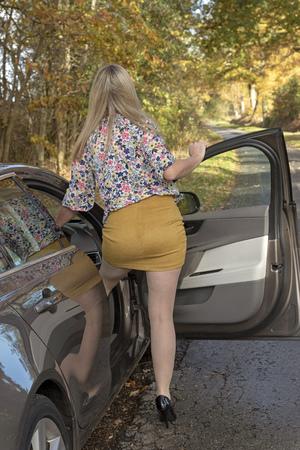 Blonde Autofahrerin, die einen engen Rock trägt, der in den Fahrersitz einer Limousine einsteigt. Standard-Bild