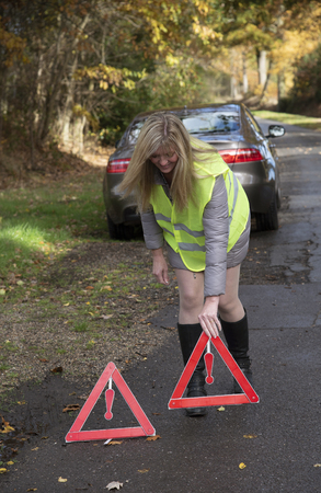 Woman driver putting out a reflective safety warning triangle at the rear of a car